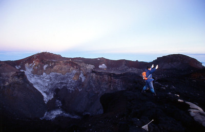 A Japanese tourist poses for another camera in front of the volcano crater. Looking west across the crater to the true summit.