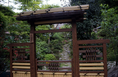 A bamboo and wood gate marks the entrance to a simple Japanese garden.