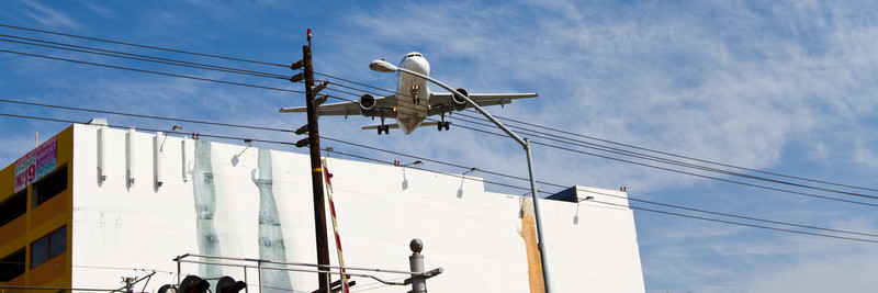 Airliner landing at Lindberg Field over the Laural Travel Center structure.