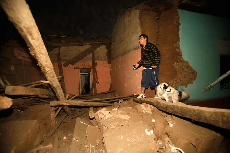 A resident of Talca, Chile, walks amid debris of a destroyed house after a devastating magnitude 8.8 earthquake struck Chile early Saturday, Feb. 27, 2010. (AP Photo/Roberto Candia). 
