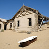 Desert sand invading dilapidated houses in the diamond mining ghost town of Kolmanskop, Namibia