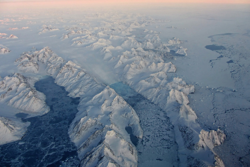 Rugged mountains, glaciers, icebergs and sea ice near Kap Gustav Holm, east-central Greenland