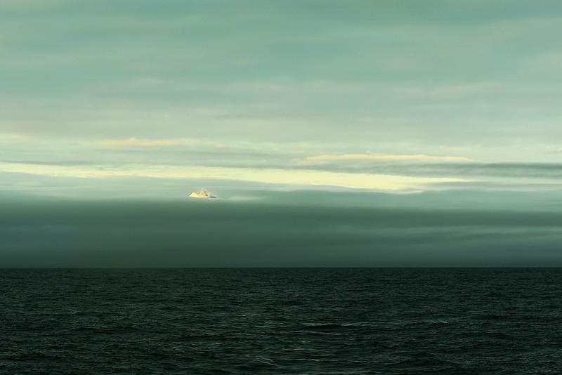 Icy peak of the Hornsundtind mountain (1429 m) piercing through thick coastal fog, Svalbard