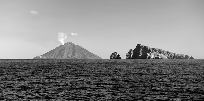 View of the active Stromboli volcano (924 m) from the island of Panarea, with the islet of Basiluzzo at right, Italy