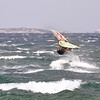 Windsurfer skimming rough seas in northeast Sardinia, Italy