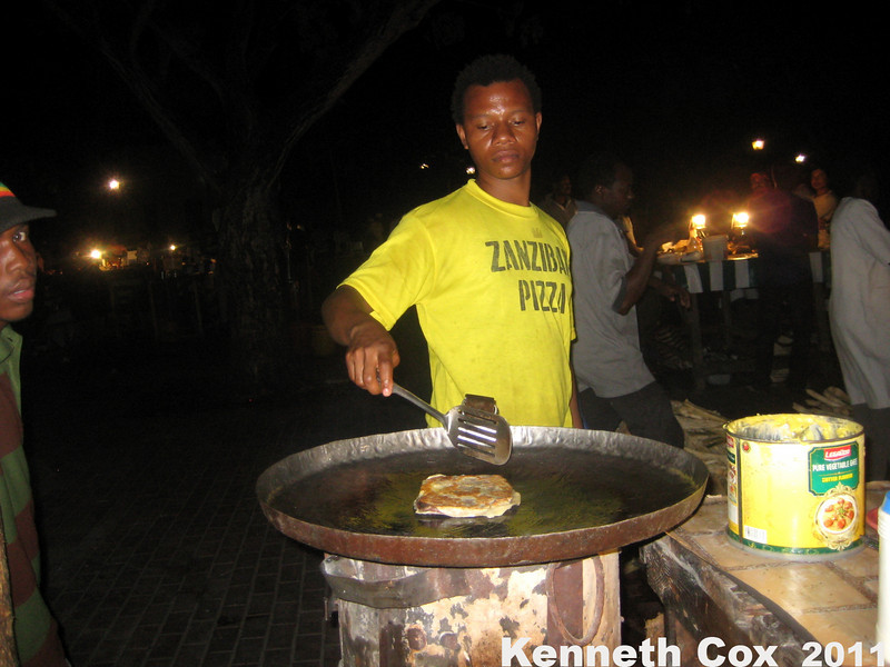 Getting a zanzibari pizza at the night market in Stone town.