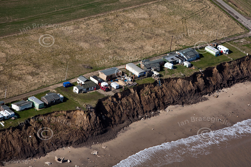 Aerial photo of houses clinging to the edge of a cliff.
