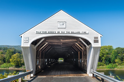 The Cornish-Windsor Bridge was built in 1866 at a cost of $9000.  This is the longest wooden bridge in the U.S. and the longest two-span covered bridge in the world.  The fourth bridge at this site, the 460-foot structure was built by Bela J. Fletcher (1811-1877) of Claremont and James F. Tasker (1826-1903) of Cornish, using a lattice truss patented by architect Ithiel Town in 1820 and 1835.  Built as a toll bridge by a private corporation, the span was purchased by the State of New Hampshire in 1936 and made toll-free in 1943.