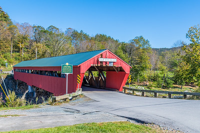 The Taftsville Covered Bridge is a rare example of early vernacular wooden truss covered bridges in the U.S.  A longtime Taftsville resident named Solomon Emmons III used no existing patented bridge truss designs and used design and construction techniques which are unique.  Constructed entirely of local wood and stone in 1836, at a cost of $1800, it is the oldest covered bridge in Windsor County, and the third oldest in the state of Vermont.  At approximately 189 feet in length at the floor, and 200 feet at the roof, it is the second longest covered bridge in Vermont.  In 2011, Tropical Storm Irene devastated the south abutment, closing the bridge for two years while extensive repairs and restoration efforts were made.