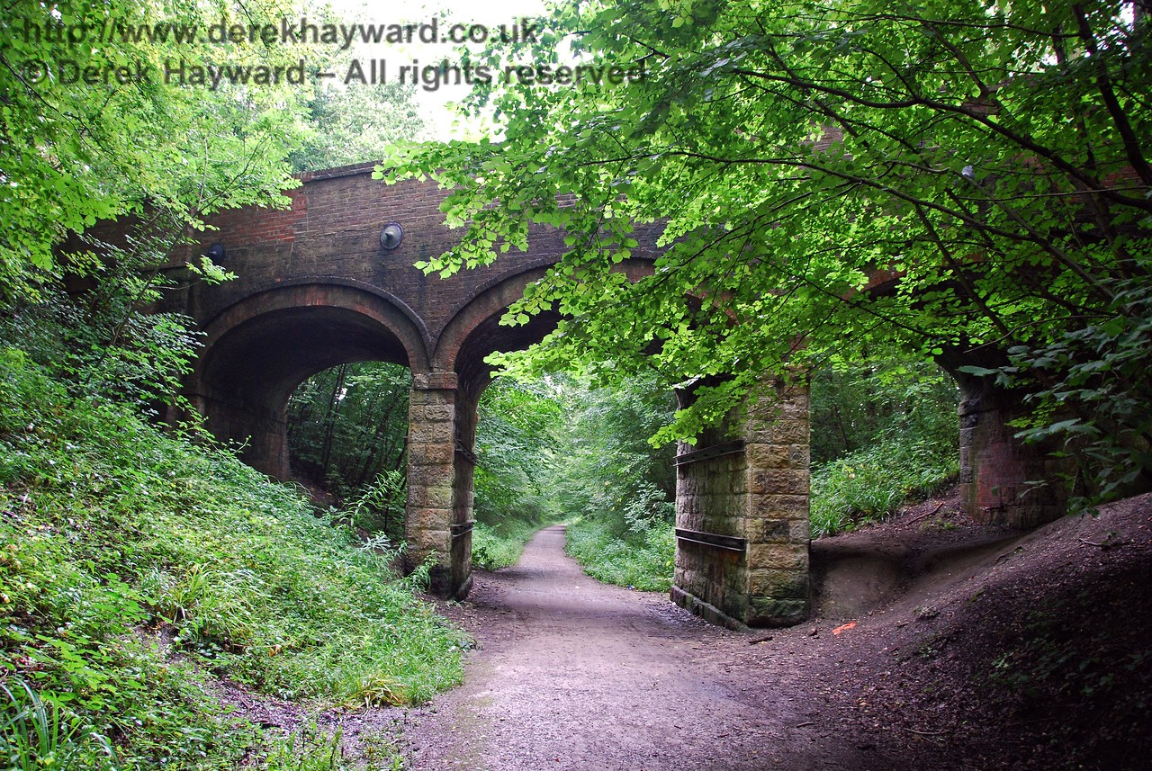 There are two railway bridges in Imberhorne Lane, which sometimes causes confusion.  This view looks west at the three arch bridge that served the Three Bridges route.  This bridge has a rather odd stone and brick combination which suggests that it is not original. The brick section shows evidence of repairs and tie-rods. There is another large single arch bridge which takes the road over the line that ran south from East Grinstead, and which is now part of the Bluebell Railway. 07.08.2009