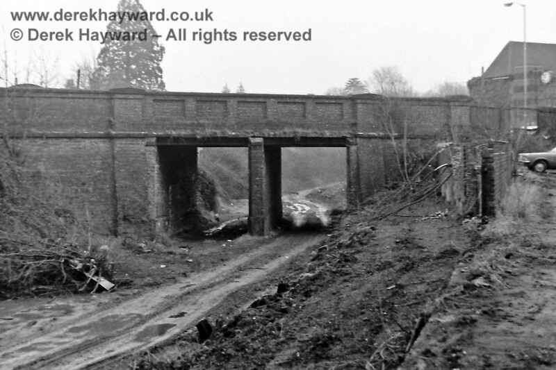 """Further east, this is the old London Road bridge (on the line to Forest Row), pictured in December 1975, when the area was looking very sorry for itself, the track having been lifted and the old ballast bulldozed.  Many years ago this was also the site of the second East Grinstead station, which was opened in 1866. A station building spanned the tracks in front of the bridge and the platforms ran south in the earth area past the camera.  The station was replaced by a third station in 1882 when the line from Lewes opened (the """"Low Level"""" station) but the London Road site actually remained open until 1883. The redundant structure was finally removed in 1908.  The bridge in the picture was demolished in 1978 as part of road improvements.  Eric Kemp retains all rights to this image."""