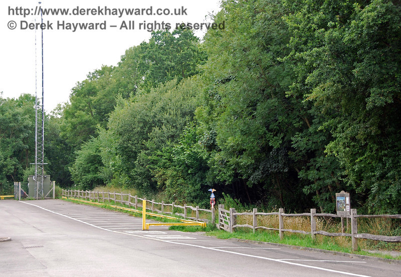 Moving closer to the site of the old junction, the line to Three Bridges passes to the right of the radio mast, and the double track to London curved right between the two signs in the foreground. The trees conceal the heavily overgrown cutting that curves north. 26.07.2009