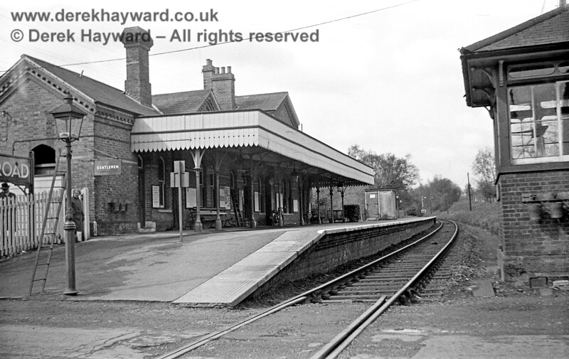 I am grateful to John Attfield for allowing me to use some of his pictures in this gallery.  Grange Road station, looking west across the level crossing on 20 April 1965, when the line was still open.  An eastbound Home signal can be seen  west of the platform, but the station had no Starting signal adjacent to the signal box to protect the level crossing.  On the left John's Mother stands in the gate, with his Father discreetly in the background behind the running-in board.  The family were keen ramblers and visited a number of stations on this day, arriving on the 409 bus shown in the Forest Row gallery.   John Attfield retains all rights to this image.
