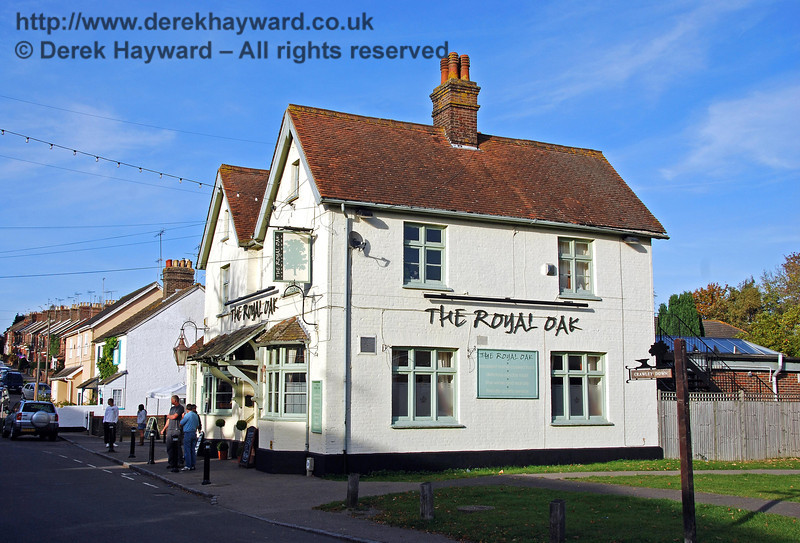 The Royal Oak public house, looking north.  This area is known as Crawley Down, and for many years the station was called Grange Road for Crawley Down and Turners Hill. Like many rural stations the name did not actually reflect the position of the station, and unwary visitors for Turners Hill faced a long steep uphill walk to their destination. The name of the station was later shortened to Grange Road. The pub serves as a point of reference to locate the site of the station. A level crossing was positioned roughly where the camera is situated, with trains running left to right across the picture alongside the pub. The small Crawley Down signpost on the right of the picture is probably sited approximately within the track bed. 18.10.2009