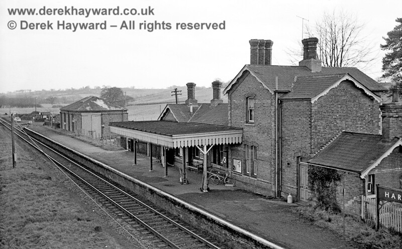 I am grateful to John Attfield for allowing me to use some of his images in this gallery. Hartfield Station is pictured from the road bridge on 6 January 1966, with a churn outside the door, a bike in the rack, and two luggage trolleys leaning against the pillars ready for use.  There is plenty of coal in the goods yard but greatly enlarging the image does not immediately reveal the goods siding upon which the car would be parked.  Perhaps the track was just dirty at the time.  John Attfield retains all rights to this image.