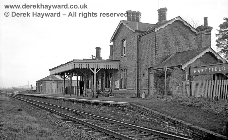 "Hartfield station looking east from track level on 6 January 1966.  The Station Master's door on to the platform is marked ""Private"", and an enlarged image reveals that a loading gauge survives in the goods yard.  A tiny speck on the extreme left of the picture is a DMU either approaching or leaving the station.  John Attfield retains all rights to this image."