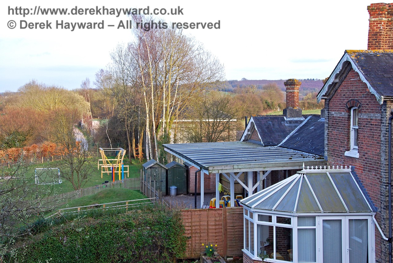 Using a slightly longer lens, this shot looks east along the track bed past Hartfield Station booking office. In the background the Goods Shed can just be seen in the trees. The canopy is not original but recreates the scene for the children who visit the building. Hartfield Station did not have a full length canopy. It started just beyond the first floor casement window and ran the length of the booking office. A tiny colour change in the brickwork beyond the conservatory roof marks the position in which the canopy was originally fitted. 22.03.2009