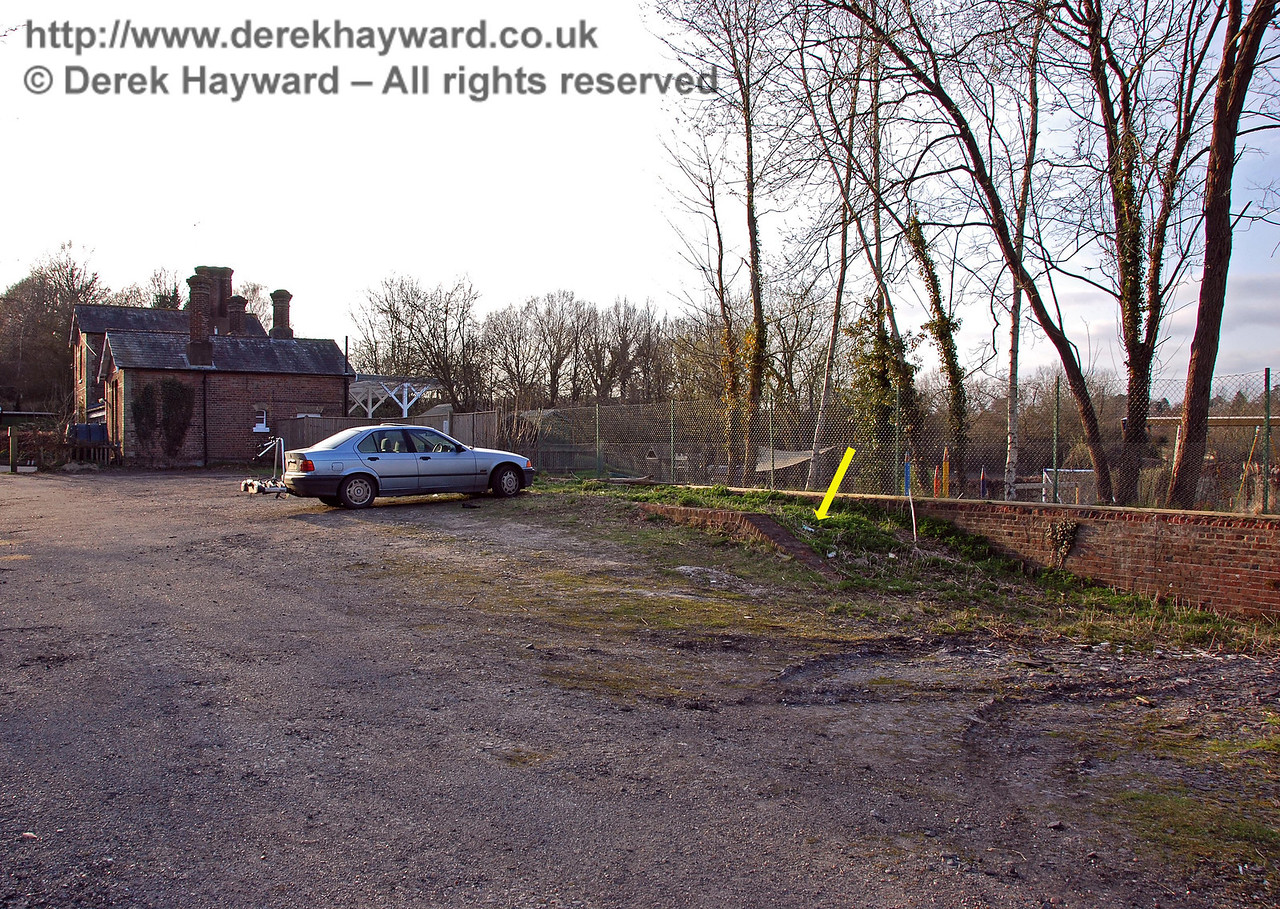 Looking west at land beyond Hartfield Station Goods Shed, the infilled loading dock is marked by an arrow.  In earlier years the parked car would have fallen into the loading dock and on to the track. 22.03.2009