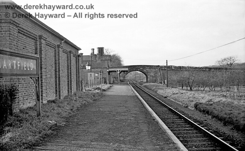Hartfield station looking west on 6 January 1966 from a position adjacent to the goods shed.  Note that the otherwise straight track had to deviate slightly to pass under the road bridge.  There was only ever  a single line in this section of the route, although many of the bridges were built to cater for double track.  John Attfield retains all rights to this image.