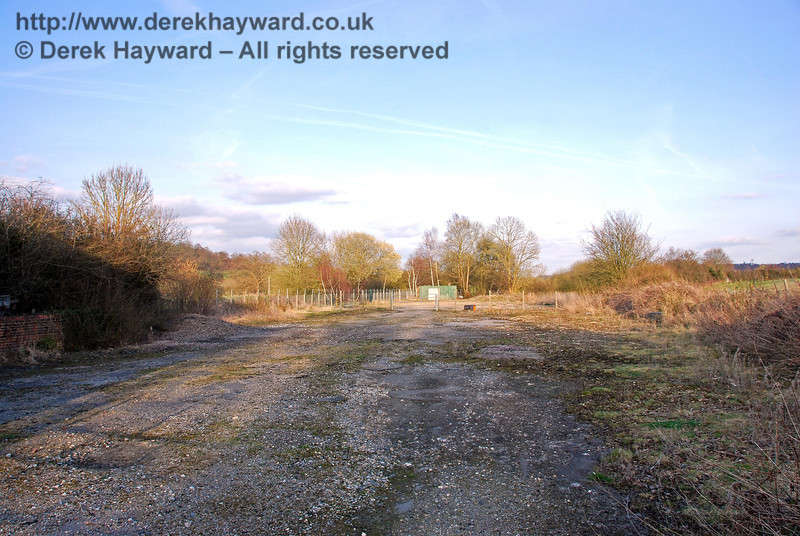 Looking east along Hartfield Station goods yard. In addition to the siding leading to the goods shed, which would have been on the left, a long siding ran the length of the goods yard on the right, following roughly the line of the rough grass adjacent to the hard standing. An external crane was provided, and the base would have been roughly where the small circular mound rises from the ground in the centre of the picture. 22.03.2009