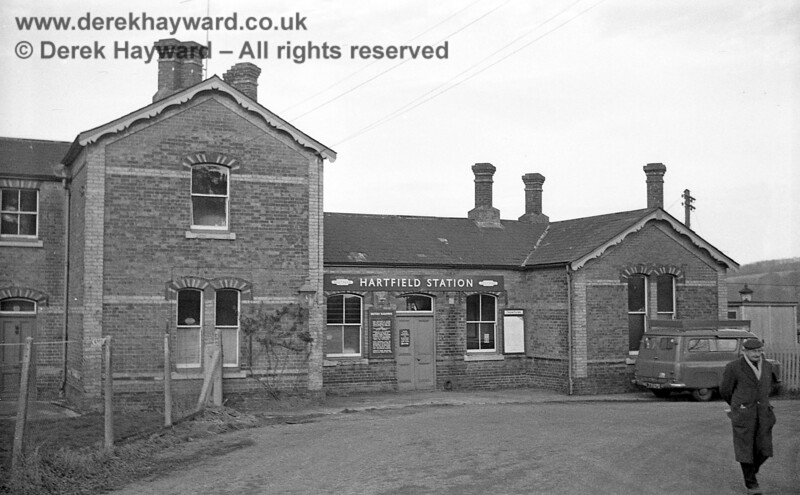 The forecourt and entrance to the booking hall at Hartfield station pictured on 6 January 1966.  The photo catches the majority of the Station Master's house on the left, with his front door just in shot.  A ghostly figure watches the photographer from the upper left window.  The railway seems to have erected a fence either to provide a front garden or to keep travellers away from his door..!  John Attfield retains all rights to this image.