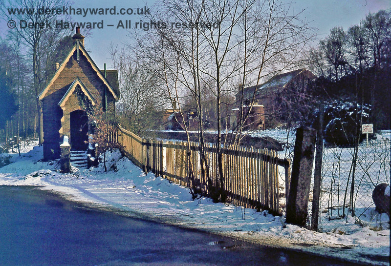 "I am grateful to Nick Mander for allowing me to use this image of Rowfant Station taken in the 1970s.  The station had closed in January 1967, but the track still seems to be in position in the platform area, just poking through the snow.  On the right someone has erected a ""Private, Danger, Keep Out"" notice, no doubt referring to the fuel depot.  On the right wall of the coachman's porch a black hole can be seen where the GPO had removed the station post box.  The hole was later professionally bricked up.  Nick retains the copyright of this image."