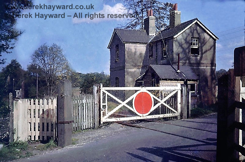 "I am grateful to Nick Mander for allowing me to use this delightful image of Compasses Crossing taken in about August 1967.  Images of this crossing are very rare.  The line had closed in January 1967 but the gates were still in situ.  Beyond the top right of the gate the words ""Closing Down"" can just be seen chalked on the side of the gatekeeper's wooden hut.  Beyond the crossing gate a lineman's hut can also be seen.  Modern road users will note how narrow the crossing then was.  Although the line was closed there are believed to have been some isolated movements over the crossing bound for the Rowfant goods facility.  Nick retains the copyright of this image."