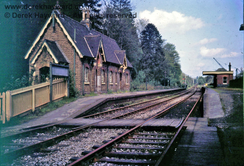 I am grateful to Nick Mander for allowing me to use this image of Rowfant Station taken in about August 1967.  The station had closed in January 1967, but the track and signals were still in situ.  At the eastern end of the platform are a starting signal with a shunt arm below it.  To the right is a ground signal which probably authorised eastbound movements from the westbound platform.  In the far distance is a tall westbound home signal.  The crane on the right is within the goods facility.  Behind the camera is the diagonal level crossing.  Nick retains the copyright of this image.