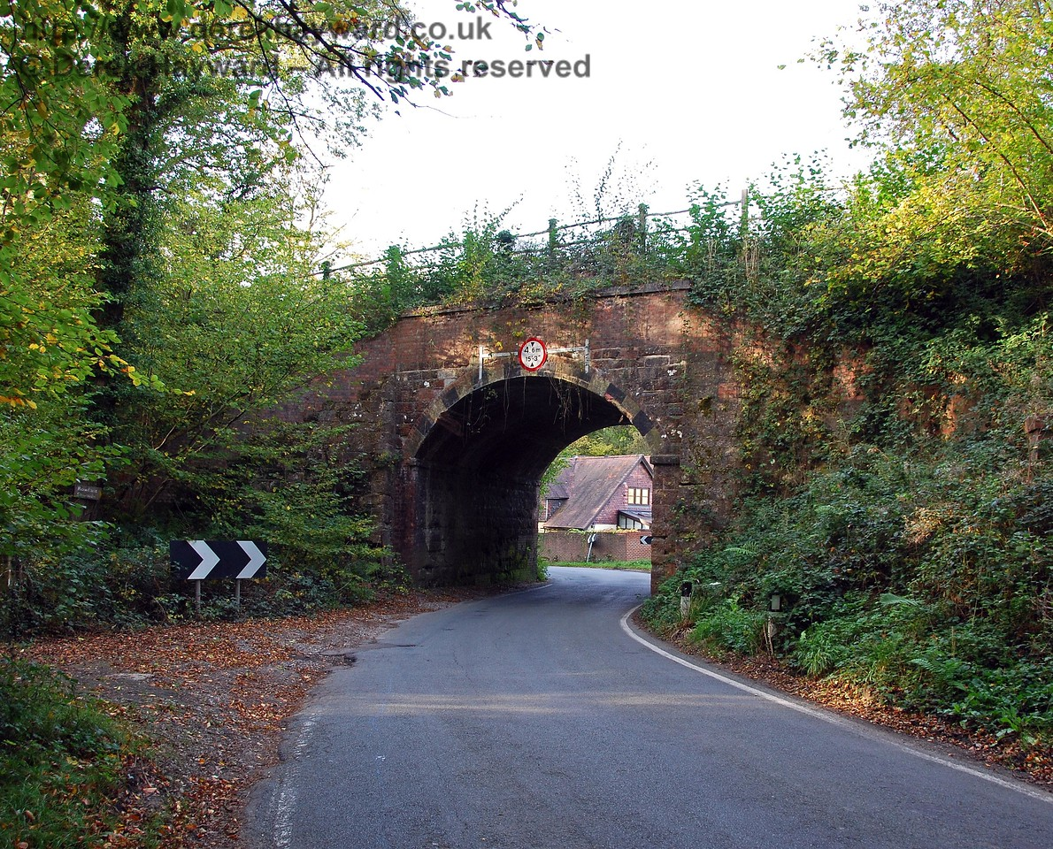 East of Rowfant Station the track passed over a country lane on an arched bridge.  This view looks north.  The trackbed above carries the Worth Way. 18.10.2009
