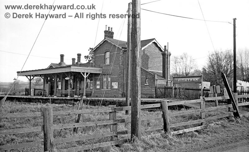 Withyham Station looking south towards the single platform and station buildings on 6 January 1966.  A narrow road runs across the level crossing west of the station but the combined efforts of the power company and the (then) GPO manage to obstruct the vista.  John Attfield retains all rights to this image.