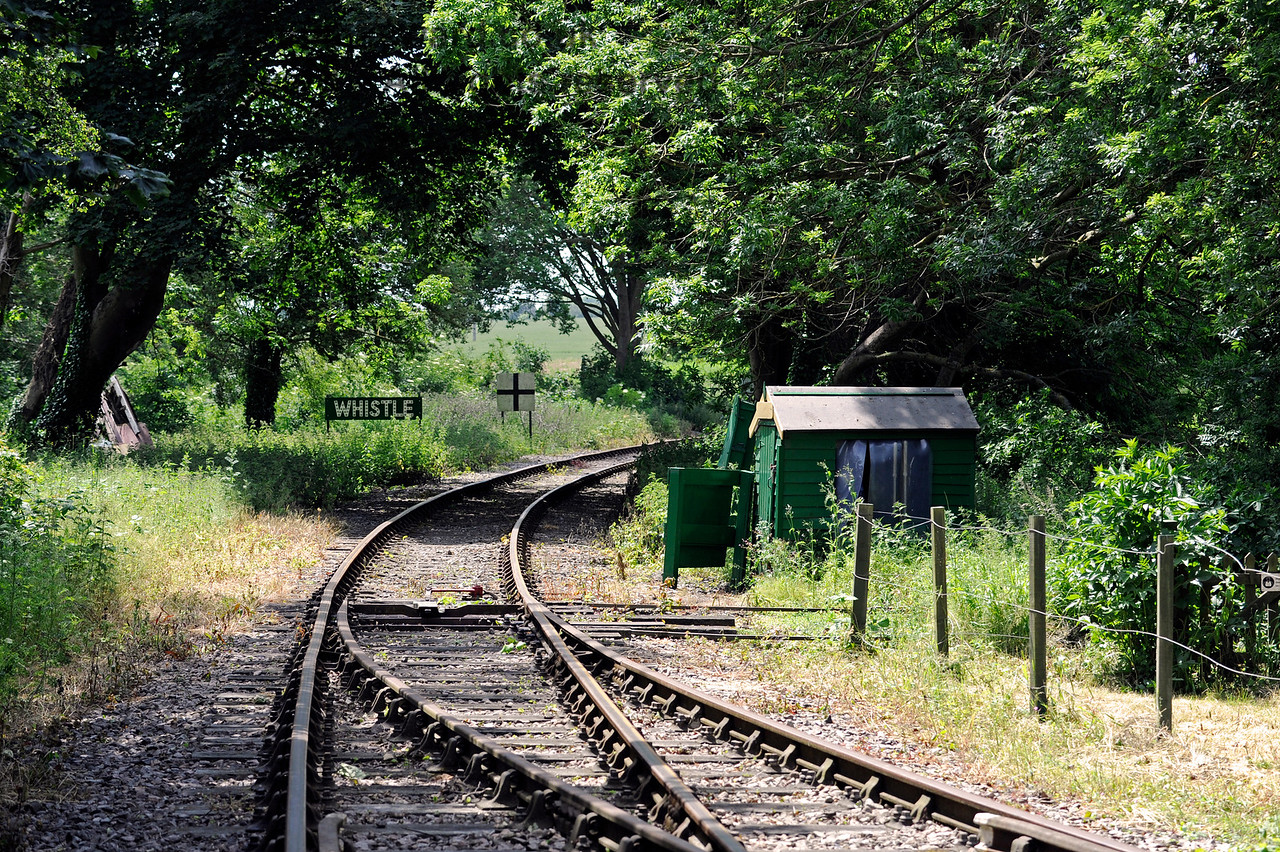 Looking west from Eythorne Station, East Kent Railway.  The Whistle and black cross warning sign refer to a crossing out of view around the bend.  The ground frame for the points is within the hut. 17.06.2015  11384