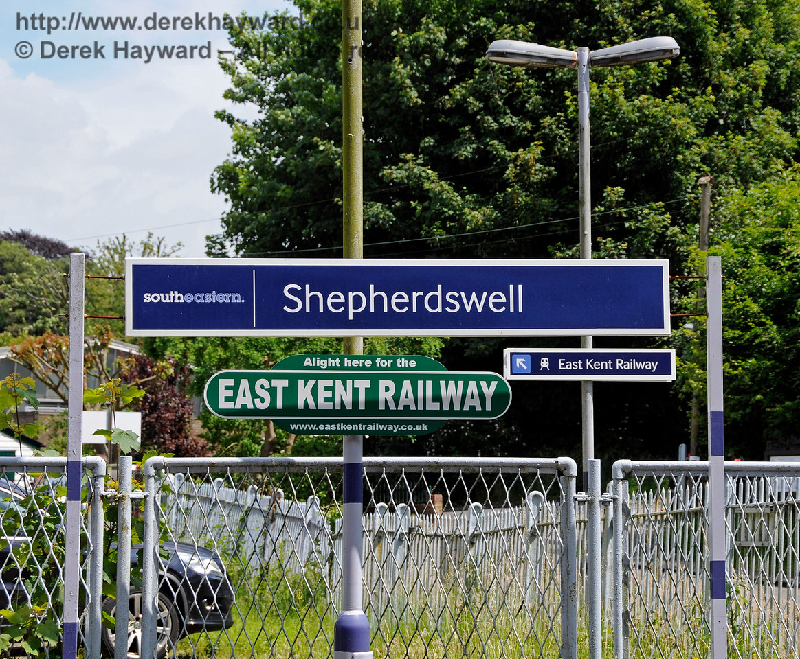 Shepherds Well (or Shepherdswell) Station, Network Rail, showing the new South Eastern signage which makes the station name one word.  On old railway maps it is Shepherds Well, which was the name shown on earlier station boards, and which is still on the signal box.  Signs for the East Kent Railway also appear. 17.06.2015  12772