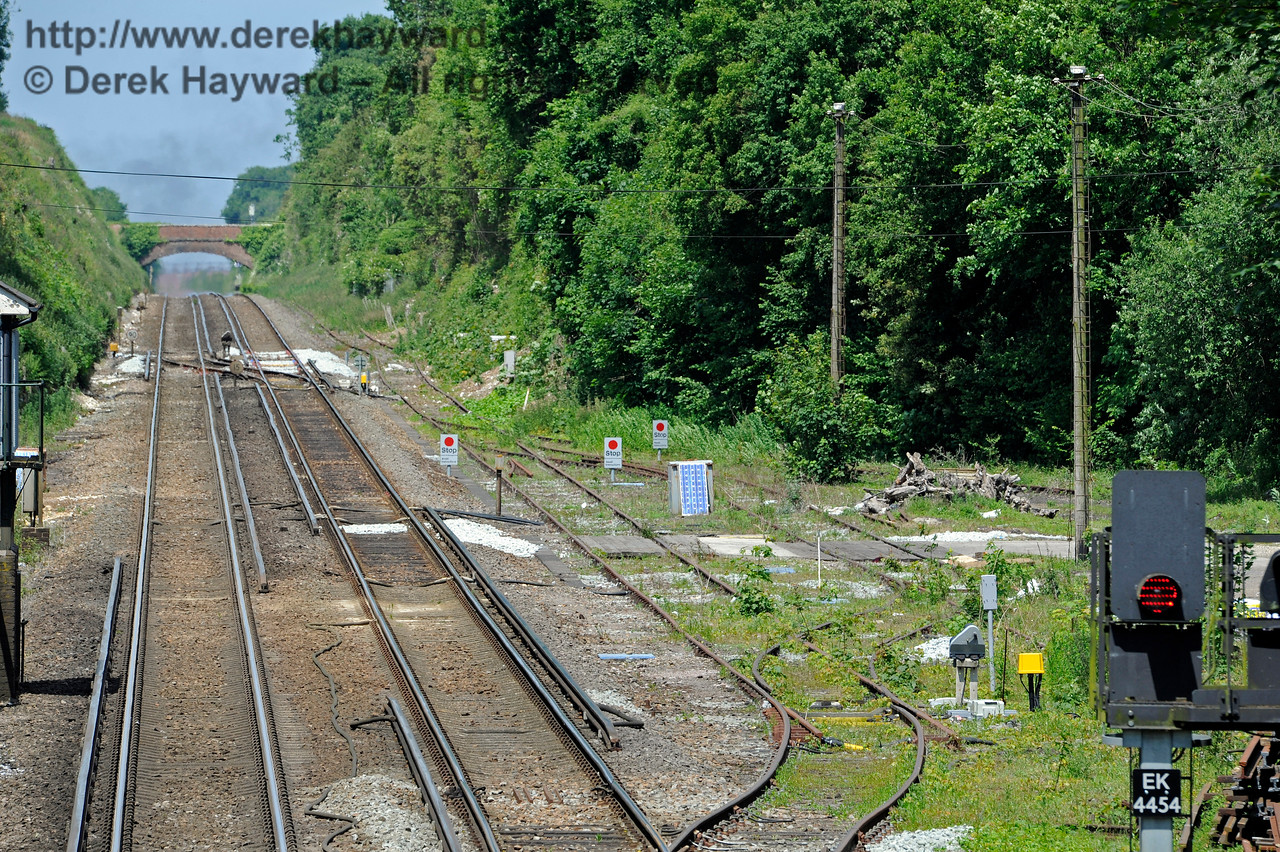 A further view of the sidings north of Shepherds Well (or Shepherdswell) Station, Network Rail. To the left of the red signal is the back of a modern LED shunt signal which controls egress from the sidings.  There is extensive rail infrastructure training at the EKR by contractors learning to work on Network Rail, and the roadway across the sidings is assumed to be an infrastructure access.  17.06.2015  11377