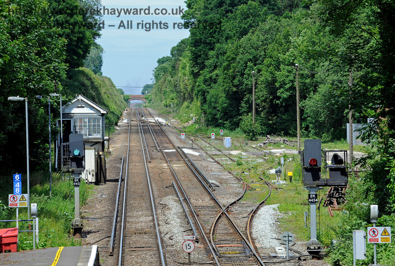 A wider view of the sidings north of Shepherds Well (or Shepherdswell) Station, Network Rail.  The East Kent Railway are hoping to acquire these sidings from Network Rail, which might provide indirect rail access from the main line via a shunt movement up the long siding in the distance.  The rail link leading into the EKR is easy to reinstate, and goes through the trees to the right of the right-hand Stop board in the distance.  17.06.2015  11374