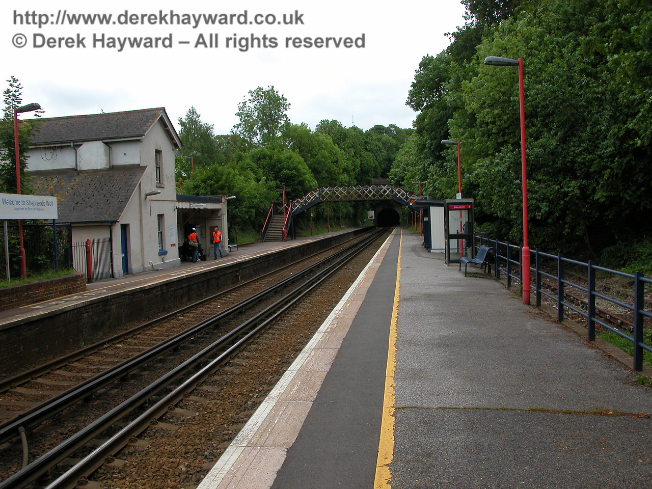 10 years earlier, Shepherds Well (or Shepherdswell) Station, Network Rail, looking south on 06.06.2005.  Note the running in sign on Platform 2 which says Welcome to Shepherds Well.  At the end of Platform 2 is an old semaphore signal with a white sighting panel behind it, and note the most unusual sight of a telephone kiosk sited on Platform 1.  Rural telephone kiosks would normally be outside railway property.
