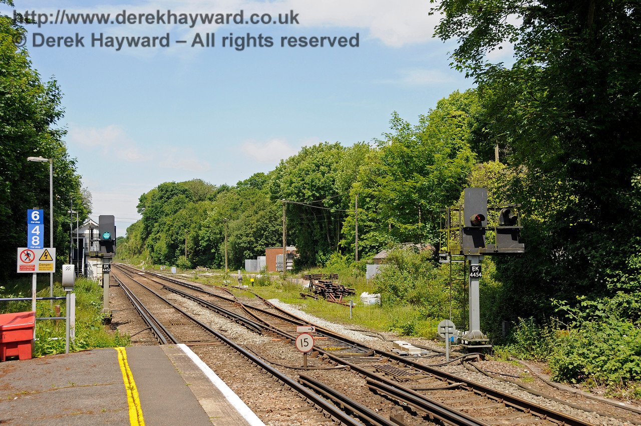 More or less the same view in 2015, with the signal box closed and new LED signals carrying EK plates (East Kent).  The refuge siding on the left has gone, as has the short siding on the right.  New buffers show the amended end of the siding.  Entry to the sidings is controlled by a shunt signal attached to EK4454, and both platforms have signals allowing departures to the north.  Shepherds Well (or Shepherdswell) Station, Network Rail. 17.06.2015  12768