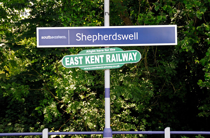 Shepherds Well (or Shepherdswell) Station, Network Rail, showing the new South Eastern signage which makes the station name one word.  On old railway maps it is Shepherds Well, which was the name shown on earlier station boards, and which is still on the signal box.  Signs for the East Kent Railway also appear. 17.06.2015  12767