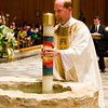 Fr. Jonathan McElhone, TOR, holding the Easter candle during the blessing of the Holy Water in the baptismal fountain.