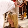 RCIA candidate Kathleen Bundy is baptized by Father Richard Eldredge, TOR, in the baptismal font of Good Shepherd.