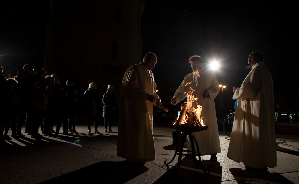 . Priests light the fire before the Easter vigil Mass at the Cathedral in Vilnius, Lithuania, Saturday, March 31, 2018. (AP Photo/Mindaugas Kulbis)