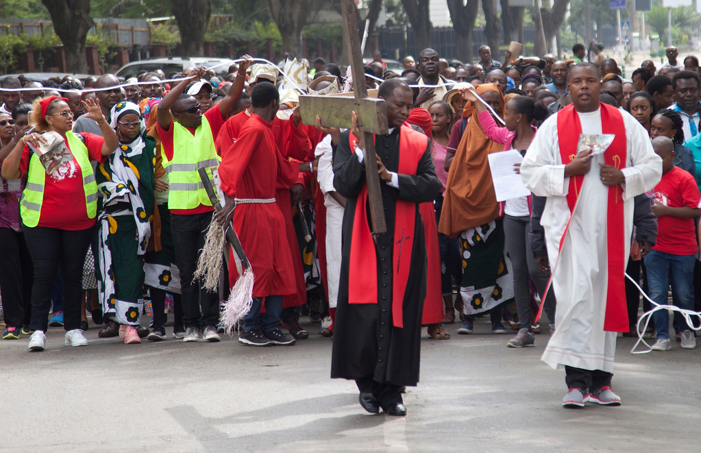 . A priest leads hundreds of followers as he carries a cross through the streets of Nairobi, Kenya, Friday, March 30, 2018, during the Holy Week. Good Friday is observed on the Friday before Easter Sunday, as Christians commemorate the passion, suffering, and death on the cross of the Lord, Jesus Christ. Many Christians spend this day in fasting, prayer, repentance, and meditation on the agony and suffering of Christ on the cross. (AP Photo/Sayyid Abdul Azim)