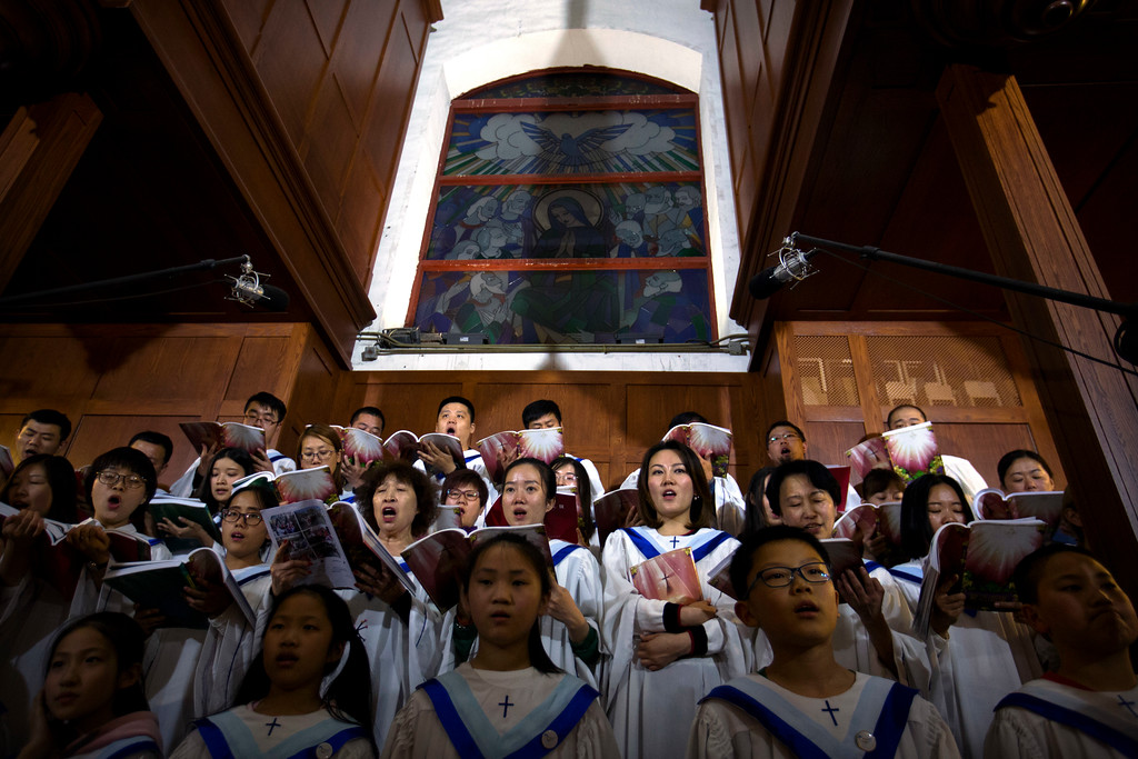 . Choir members sing a hymn during a Holy Saturday Mass on the evening before Easter at the Cathedral of the Immaculate Conception, a government-sanctioned Catholic church in Beijing, Saturday, March 31, 2018. Catholics in China prepared to celebrate Easter on Sunday amid reports that the Vatican and China\'s ruling Communist Party were in talks aimed at yielding a deal on who appoints bishops in China. (AP Photo/Mark Schiefelbein)