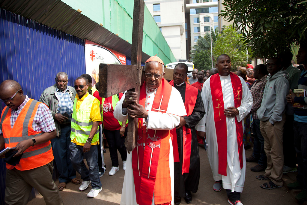 . Joined by hundred of Christians, leader of the Catholic Church in Kenya, Cardinal John Njue carries a cross through the streets of Nairobi, Kenya, Friday, March 30, 2018 during the Holy Week. Good Friday is observed on the Friday before Easter Sunday, as Christians commemorate the passion, suffering, and death on the cross of the Lord, Jesus Christ. Many Christians spend this day in fasting, prayer, repentance, and meditation on the agony and suffering of Christ on the cross. (AP Photo/Sayyid Abdul Azim)