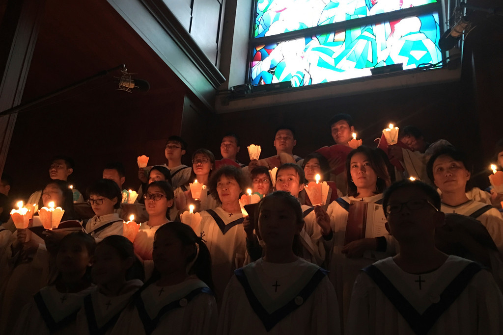 . Choir members hold candles during a Holy Saturday Mass on the evening before Easter at the Cathedral of the Immaculate Conception, a government-sanctioned Catholic church in Beijing, Saturday, March 31, 2018. Catholics in China prepared to celebrate Easter on Sunday amid reports that the Vatican and China\'s ruling Communist Party were in talks aimed at yielding a deal on who appoints bishops in China. (AP Photo/Samuel McNeil)