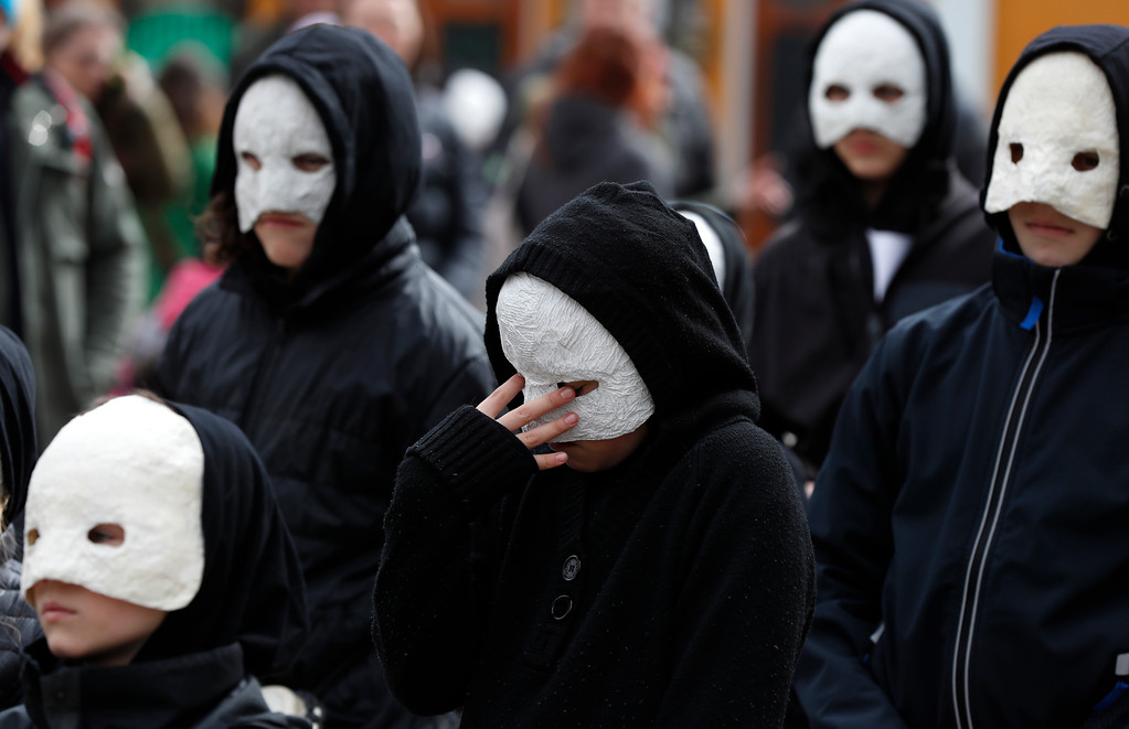 . Participants wearing masks, beating drums and pushing small carts that make a synchronized and loud sound take part in an Easter procession through the streets of Ceske Budejovice, Czech Republic, Friday, March 30, 2018. (AP Photo/Petr David Josek)