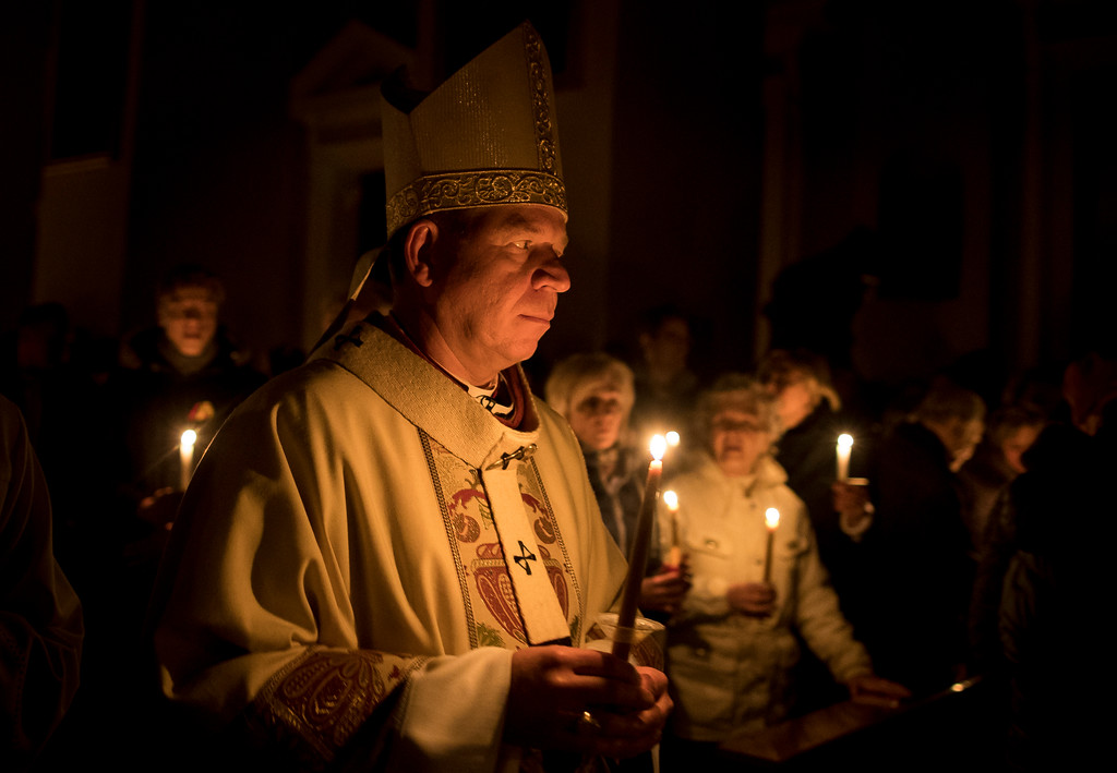 . Archbishop Gintaras Grusas and worshippers hold candles during the Easter vigil Mass in Cathedral-Basilica in Vilnius, Lithuania, Saturday, March 31, 2018. (AP Photo/Mindaugas Kulbis)