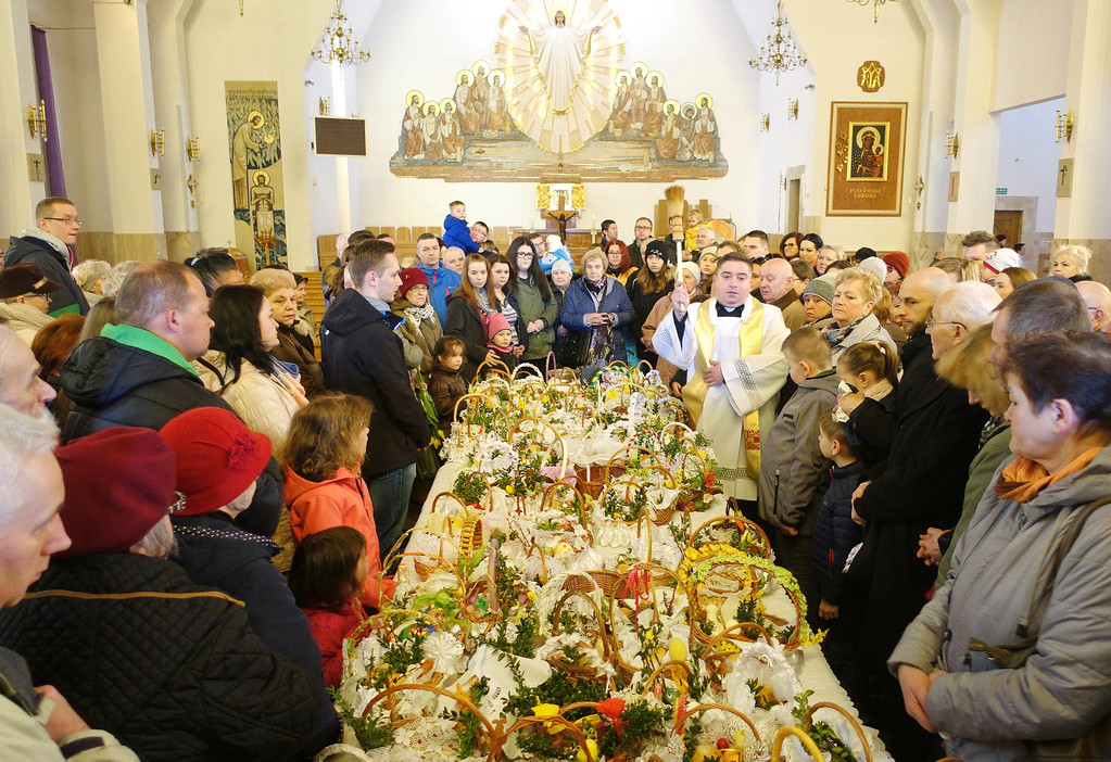 . A priest blesses baskets with food samples brought by faithful in a church in Legionowo, Poland, Saturday, March 31, 2018. Traditionally Catholic Poles bring baskets containing mainly an egg, bread, salt, pepper, sausage, horseradish, and butter to churches to be blessed on Holy Saturday, the day before Easter Sunday. (AP Photo/Alik Keplicz)