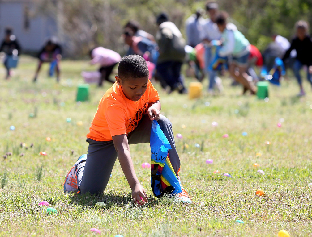 . Keegan Dunn, 8, collects a plastic Easter egg during Word Tabernacle Church\'s fourth annual Easter Explosion event at Bea Holman Park, Saturday, March 31, 2018, in Rocky Mount, N.C. (Alan Campbell/The Rocky Mount Telegram via AP)