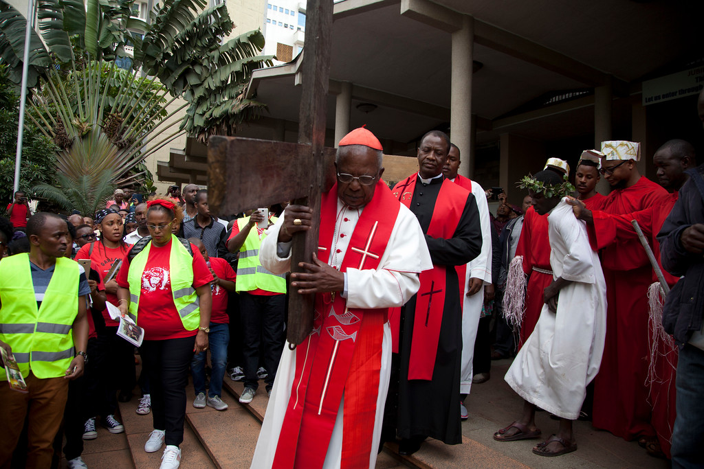 . Joined by hundred of Christians, leader of the Catholic Church in Kenya, Cardinal John Njue carries a cross through the streets of Nairobi, Kenya, Friday, March 30, 2018, during the Holy Week. Good Friday is observed on the Friday before Easter Sunday, as Christians commemorate the passion, suffering, and death on the cross of the Lord, Jesus Christ. Many Christians spend this day in fasting, prayer, repentance, and meditation on the agony and suffering of Christ on the cross. (AP Photo/Sayyid Abdul Azim)