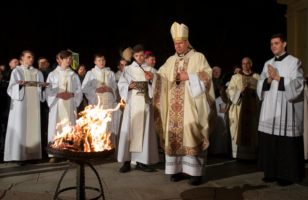 . Archbishop Gintaras Grusas performs the blessing at the Easter vigil Mass at the Cathedral in Vilnius, Lithuania, Saturday, March 31, 2018. (AP Photo/Mindaugas Kulbis)